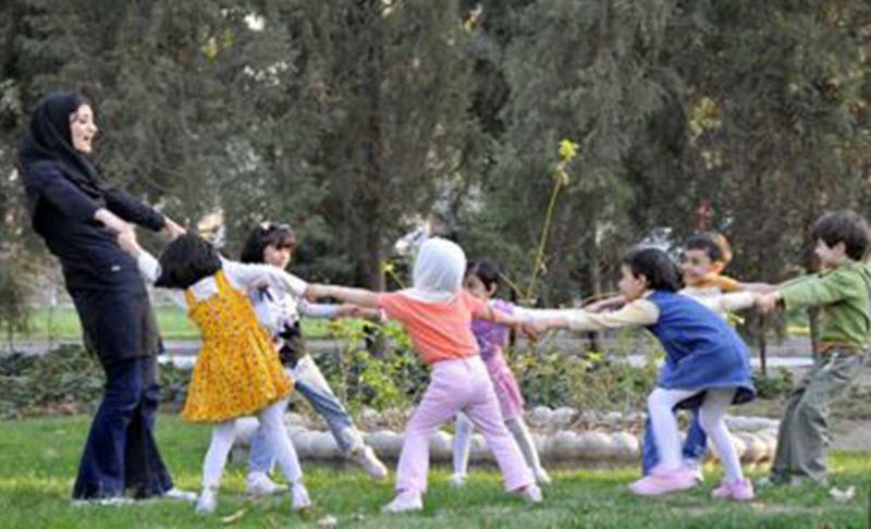 A kindergarten teacher playing with children in Iran